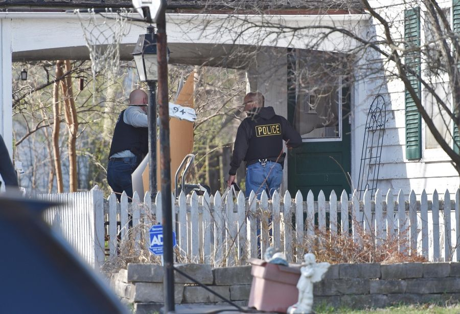 "Police carry large cardboard sheets Friday into the home of Andrew ""AJ"" Freund, 5, who has been missing since he was last seen Wednesday night at his home on Dole Avenue in Crystal Lake."