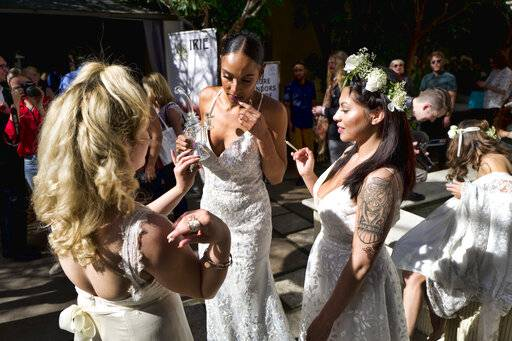 FILE - In this Jan. 26, 2019 file photo models wearing wedding dresses get ready smoke marijuana during the Cannabis Wedding Expo in Los Angeles. U.S. retail sales of cannabis products jumped to $10.5 billion last year, a threefold increase from 2017, according to data from Arcview Group, a cannabis investment and market research firm. The figures do not include retail sales of hemp-derived CBD products.