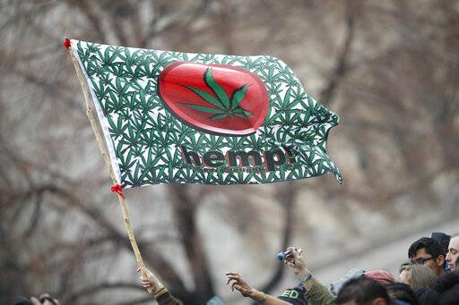 FILE - In this April 20, 2018 file photo an attendee hoists a flag during the Mile High 420 Festival in Denver. Potheads have for decades celebrated their love of marijuana on April 20, but the once counter-culture celebration that was all about getting stoned now is so mainstream Corporate America is starting to embrace it.