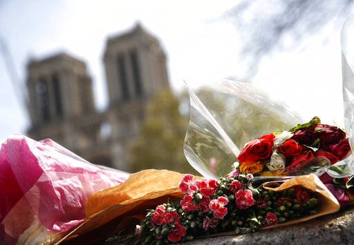 Flowers and tributes are left outside the Notre Dame Cathedral in Paris, Thursday, April 18, 2019. Nearly $1 billion has already poured in from ordinary worshippers and high-powered magnates around the world to restore Notre Dame Cathedral in Paris after a massive fire. (AP Photo/Christophe Ena)