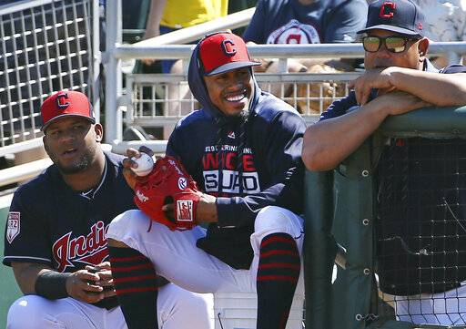 FILE - In this March 18, 2019, file photo, injured Cleveland Indians shortstop Francisco Lindor, center, smiles as he watches his teammates during the first inning of a spring training baseball game against the San Diego Padres in Goodyear, Ariz. Lindor says he's ready to make his season debut after being injured. Lindor sat out Cleveland's first 18 games with a sprained ankle he sustained during spring training in Arizona while recovering from an offseason calf injury. He's expected to be in Cleveland's lineup this weekend against Atlanta. (AP Photo/Ross D. Franklin, File)