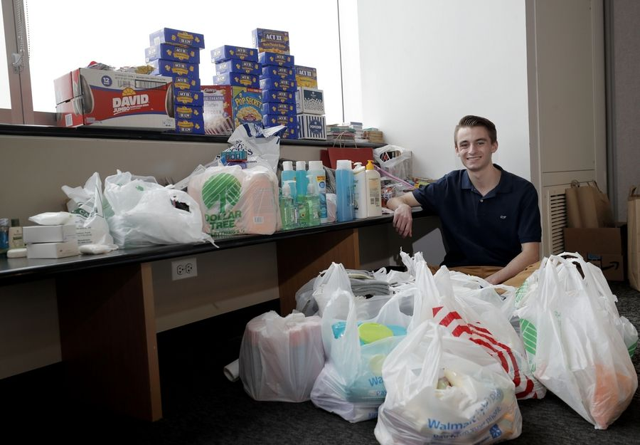 Mundelein High School student Matthew Pawlowski sits with some of the donations collected by a club he founded to benefit U.S. military personnel stationed overseas.