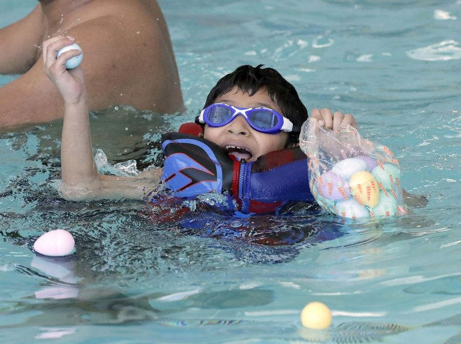 Tanush Burra, 5, of Hoffman Estates swims for eggs as kids put on their swimsuits and goggles for an Aqua Egg Hunt at the Club at Prairie Stone in Hoffman Estates Saturday.