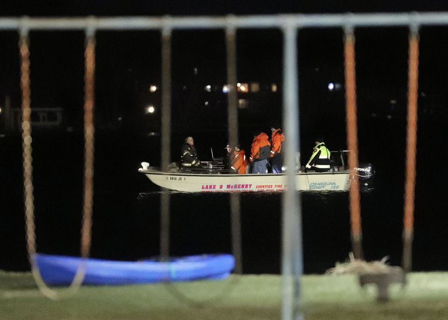 A rescue boat searches for a missing 9-year-old boy who fell into Bangs Lake in Wauconda Friday evening. He was found about noon Saturday. The lake has been closed as public safety officials worked on recovery efforts.