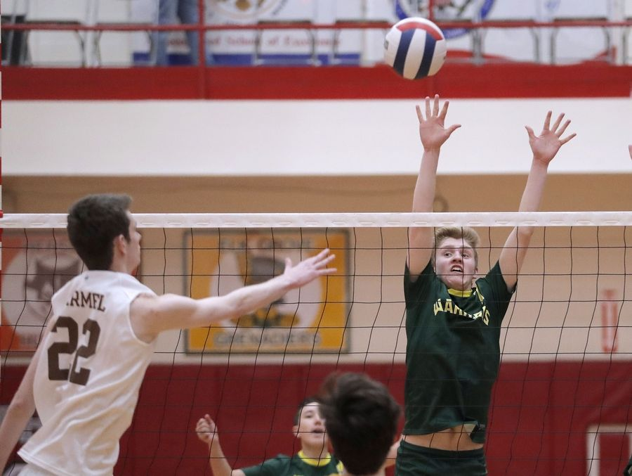 Carmel's David Foecking, left, spikes one at Waubonsie Valley's Marc Bailey during the Palatine boys volleyball tournament Saturday.