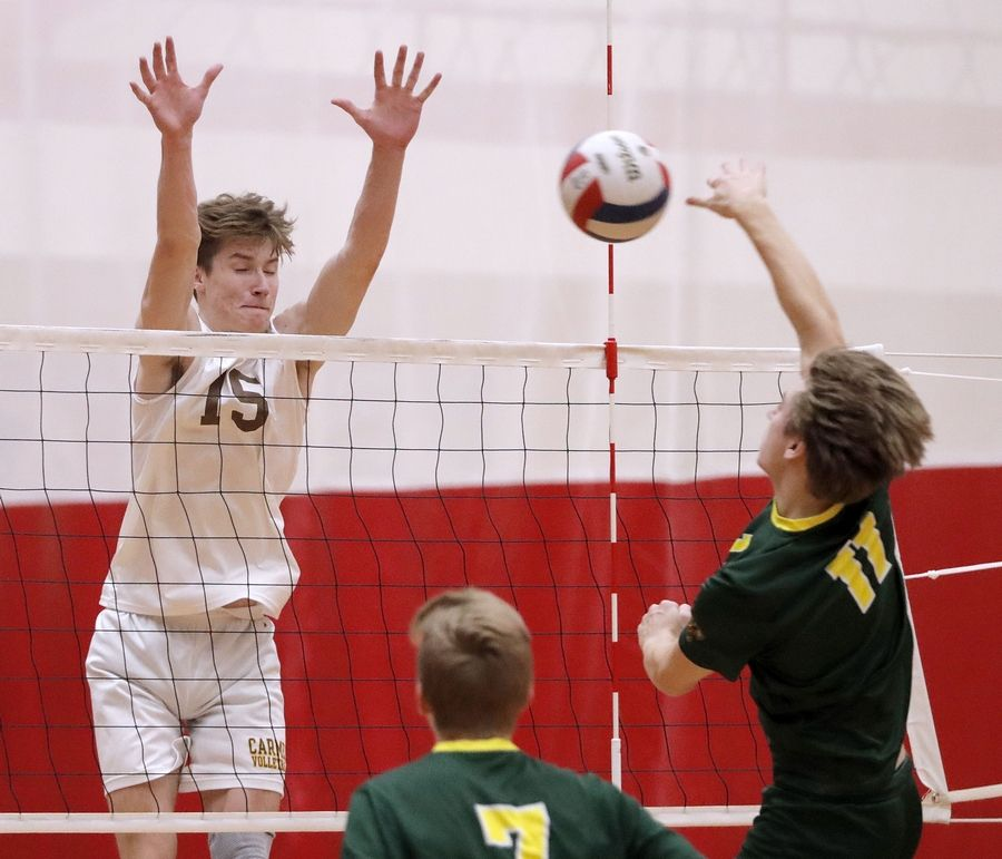 Carmel's Mike Scott, left, meets Waubonsie Valley's Ben Jordan at the net during the Palatine boys volleyball tournament Saturday.