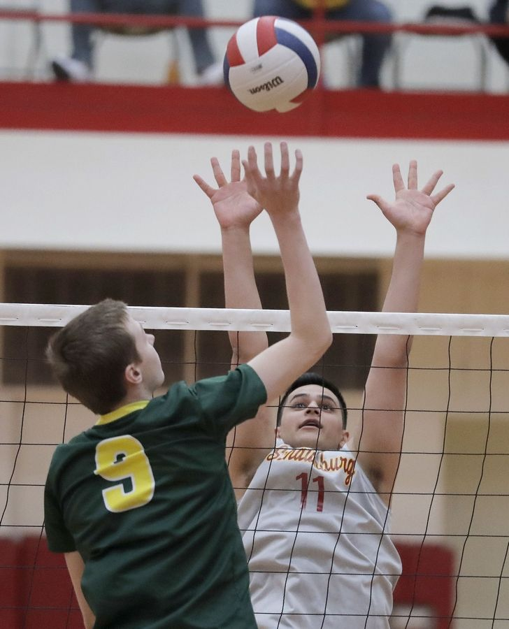 Waubonsie Valley's Ben Schwieger, left, and Schaumburg's Ashkan Madani meet at the net during the Palatine boys volleyball tournament Saturday.