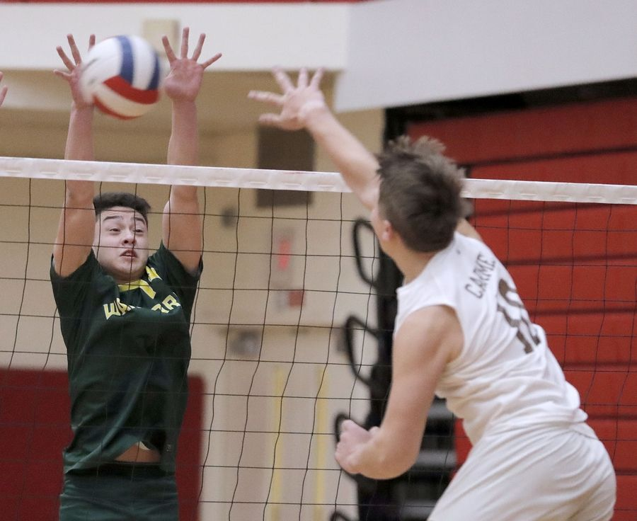 Carmel's Anderson Ptasienski, right, spikes on at Waubonsie Valley's Justin Quinto during the Palatine boys volleyball tournament Saturday.
