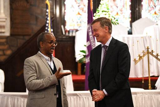 Former Colorado Gov. John Hickenlooper discusses gun control and death penalty issues with Anthony Thompson on Saturday, April 6, 2019, in Charleston, S.C. Thompson's wife was slain in a massacre that claimed nine Bible study participants at a historic black church in South Carolina. Hickenlooper, a staunch advocate for gun control legislation, visited Mother Emanuel during a campaign trip to the state as he seems the Democratic presidential nomination.