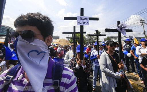 Anti-government protesters join a Stations of the Cross procession on Good Friday, carrying signs demanding the release of political prisoners in Managua, Nicaragua, Friday, April 19, 2019. Good Friday religious processions in Nicaragua's capital have taken a decidedly political tone as people have seized on a rare opportunity to renew protests against the government of President Daniel Ortega.