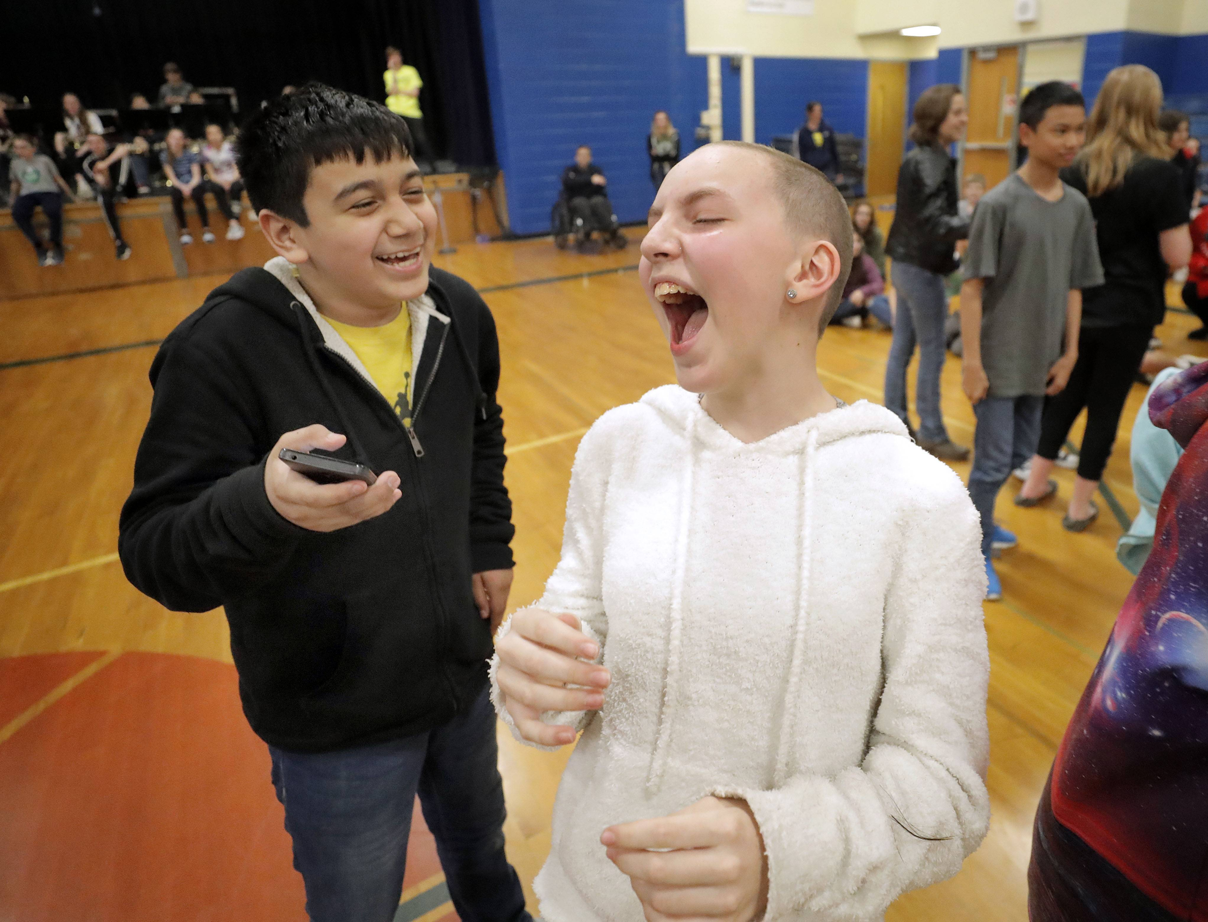 Mariana Barroso, 13, right, explodes in laughter after seeing a picture of her shaved head from friend Santiago Tellez at the Grayslake Middle School Cut & Shave Fundraiser supporting childhood cancer research for the St. Baldrick's Foundation Thursday.