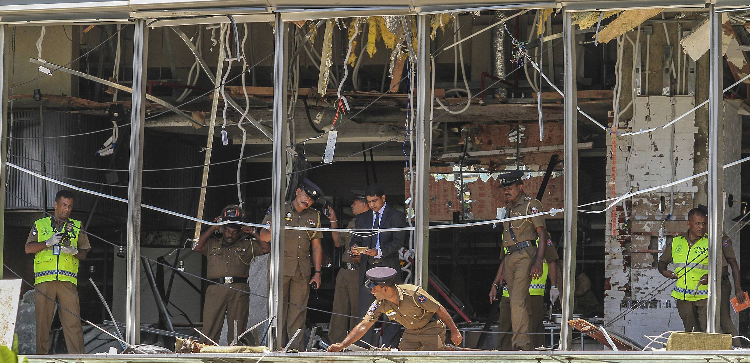 A Sri Lankan Police officer inspects a blast spot Sunday at the Shangri-la hotel in Colombo, Sri Lanka. More than hundred were killed and hundreds more hospitalized with injuries from eight blasts that rocked churches and hotels in and just outside of Sri Lanka's capital on Easter Sunday, officials said, the worst violence to hit the South Asian country since its civil war ended a decade ago.