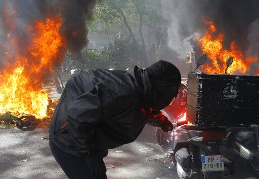 A protestor lights a motorbike on fire during a yellow vest demonstration in Paris, Saturday, April 20, 2019. French yellow vest protesters are marching anew to remind the government that rebuilding the fire-ravaged Notre Dame Cathedral isn't the only problem the nation needs to solve. (AP Photo/Michel Euler)