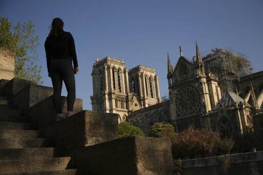 A woman stands on steps near the Notre Dame Cathedral in Paris, Saturday, April 20, 2019. Rebuilding Notre Dame, the 800-year-old Paris cathedral devastated by fire this week, will cost billions of dollars as architects, historians and artisans work to preserve the medieval landmark. (AP Photo/Francisco Seco)