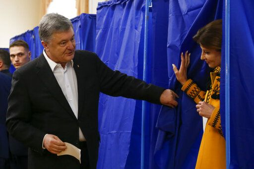 Ukrainian President Petro Poroshenko helps his wife Maryna to leave a booth at a polling station, during the second round of presidential elections in Kiev, Ukraine, Sunday, April 21, 2019. Top issues in the election have been corruption, the economy and how to end the conflict with Russia-backed rebels in eastern Ukraine.