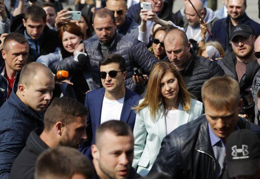 Ukrainian comedian and presidential candidate Volodymyr Zelenskiy, center left, and his Olena Zelenska, second right, arrive at a polling station, during the second round of presidential elections in Kiev, Ukraine, Sunday, April 21, 2019. Top issues in the election have been corruption, the economy and how to end the conflict with Russia-backed rebels in eastern Ukraine.