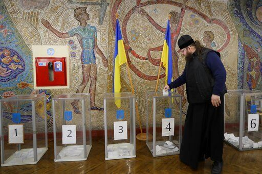 An Orthodox priest casts his ballot at a polling station, during the second round of presidential elections in Kiev, Ukraine, Sunday, April 21, 2019. Top issues in the election have been corruption, the economy and how to end the conflict with Russia-backed rebels in eastern Ukraine.