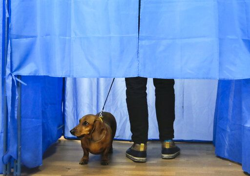 A dog looks out of a voting cabin as a man casts his vote during the second round of presidential elections in Kiev, Ukraine, Sunday, April 21, 2019. Top issues in the election have been corruption, the economy and how to end the conflict with Russia-backed rebels in eastern Ukraine.