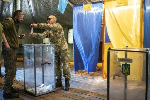 A Ukrainian government soldier demonstrates his ballot at a polling station, during the second round of presidential elections near a front line in Donetsk region, eastern Ukraine, Sunday, April 21, 2019. Top issues in the election have been corruption, the economy and how to end the conflict with Russia-backed rebels in eastern Ukraine.