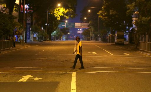 A Sri Lankan man walks across a deserted street during a curfew in Colombo, Sri Lanka, Sunday, April 21, 2019. More than two hundred people were killed and hundreds more injured in eight blasts that rocked churches and hotels in and just outside Sri Lanka's capital on Easter Sunday.