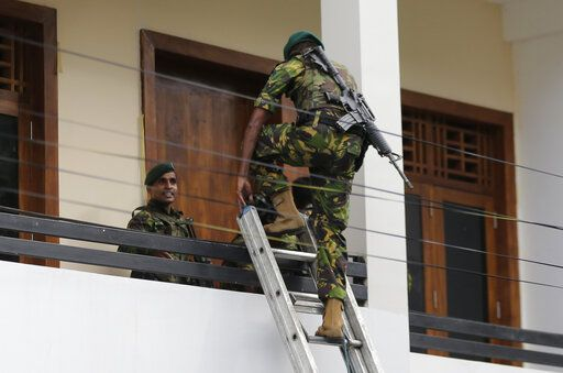 A Sri Lankan police commando enters a house suspected to be a hideout of militants following a shoot out in Colombo, Sri Lanka, Sunday, April 21, 2019.  More than hundred were killed and hundreds more hospitalized with injuries from eight blasts that rocked churches and hotels in and just outside of Sri Lanka's capital on Easter Sunday, officials said, the worst violence to hit the South Asian country since its civil war ended a decade ago.