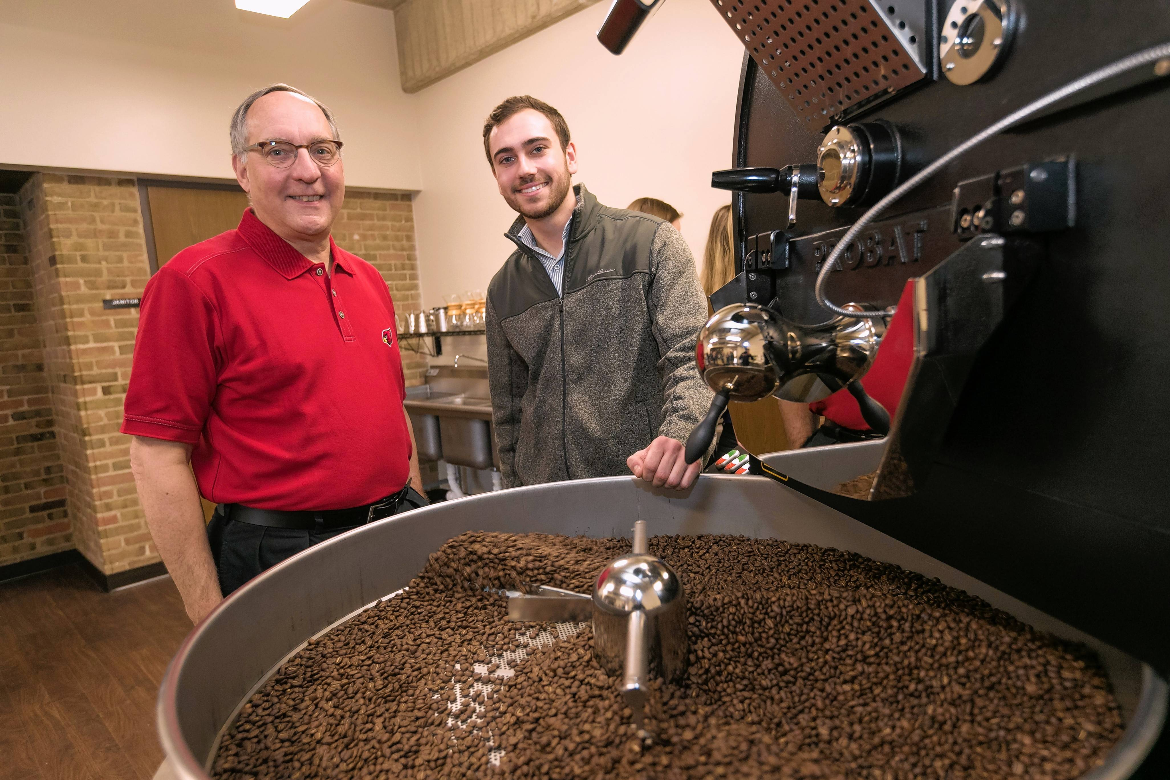 "Jim McDermet, a former Starbucks executive and the chairman of the North Central College board of trustees, stands beside entrepreneur in residence Connor McGury, right, during the college's ""First Crack"" event kicking off its new Coffee Lab."