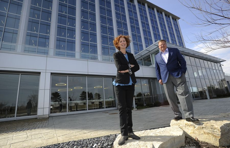 "Gina and Jim Labuz of Mid-States Glass & Metal of Niles stand in front of the Arthur J. Gallagher headquarters building in Rolling Meadows where their company did the glass and metal work. ""Gallagher gave us an opportunity to show the complexity of work we can handle,"" Jim Labuz said."