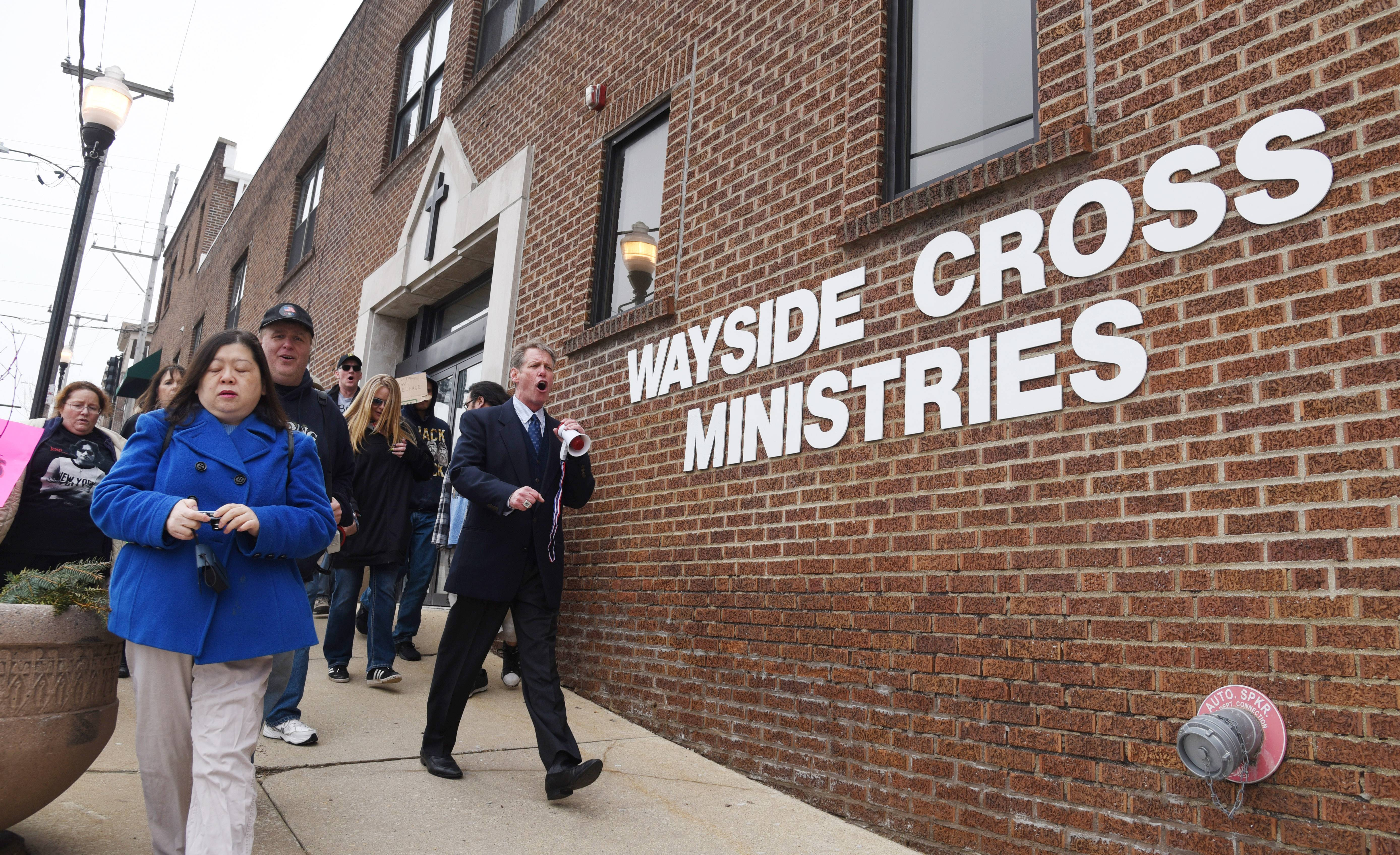 "Aurora resident Matt Harrington leads a march April 5 past the Wayside Cross Ministries facility on East New York Street in Aurora. The protest was organized over the mission accepting ""Ripper Crew"" murderer Thomas Kokoraleis as a resident in one of its programs."