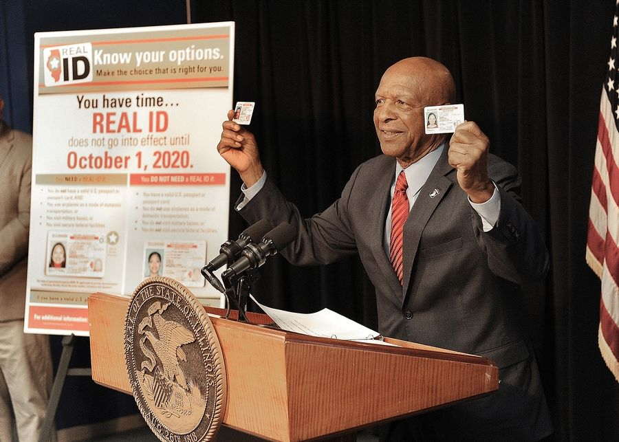 Secretary of State Jesse White holds an example of a REAL ID card in his right hand and a standard's driver's license in his left.