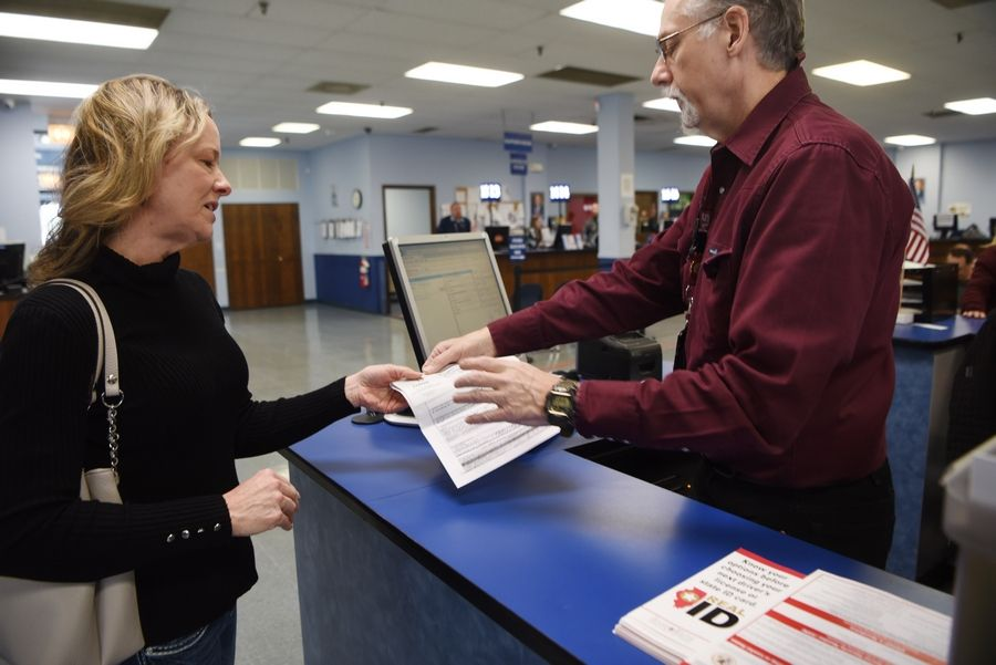 Sue Catomy of Mount Prospect receives REAL ID information on Friday while being assisted by Wendell Howell at the state driver's license facility in Schaumburg.