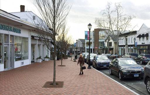 FILE - In this Jan. 26, 2017, file photo, a woman walks near shops in downtown Westport, Conn. The boom market in small businesses is showing signs of cooling. The number of small business sales counted by online market BizBuySell.com fell 6.5% during the first quarter from the same period of 2018, following a 6% fourth quarter drop.(AP Photo/Michael Melia, File)