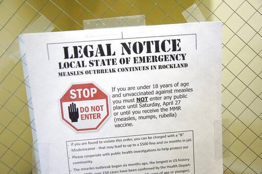 FILE - This March 27, 2019 file photo shows a sign explaining the local state of emergency because of a measles outbreak at the Rockland County Health Department in Pomona, N.Y. Outbreaks in New York state continue to drive up U.S. measles cases, which remain on pace to set a record for most illnesses in 25 years. (AP Photo/Seth Wenig, File)