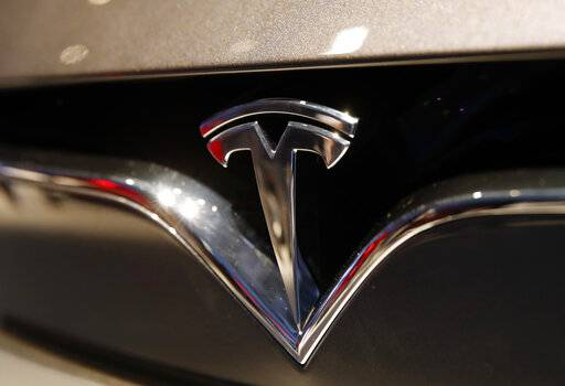 FILE- This Oct. 3, 2018, file photo shows a Tesla emblem at the Auto show in Paris. Tesla CEO Elon Musk appears poised to transform the company's electric cars into driverless vehicles in a risky bid to realize a bold vision that he has been floating for years. The technology required to make that quantum leap is scheduled to be shown off to Tesla investors Monday, April 22, 2019, at the company's Palo Alto, Calif., headquarters. (AP Photo/Christophe Ena, File)