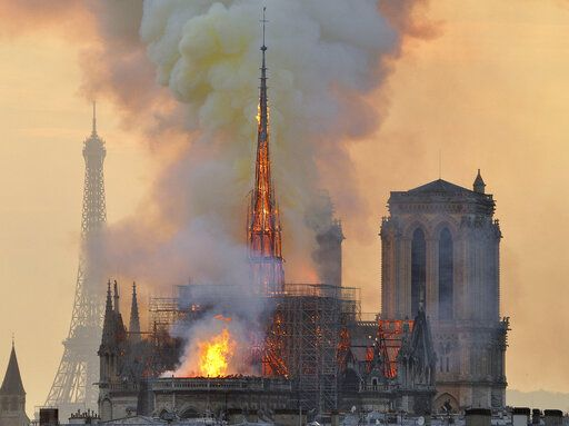"FILE - In this file photo dated Monday, April 15, 2019, with the Eiffel Tower behind, left, flames and smoke rise from the blaze at Notre Dame Cathedral in Paris that destroyed its spire and its roof but spared its twin medieval bell towers, and prompted a frantic rescue effort to save its most precious artefacts.  The recent devastating Notre Dame fire in Paris was a warning bell that all of Europe needs to hear, since so many monuments and palaces across the continent are in need of better upkeep according to European officials.  ""We are so used to our outstanding cultural heritage in Europe that we tend to forget that it needs constant care and attention,� Tibor Navracsics, the European Union's top culture official, told The Associated Press."