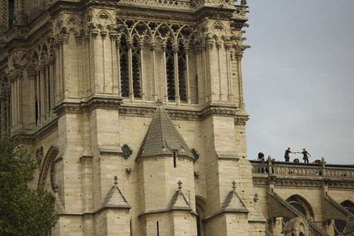 Technicians work on top of the Notre Dame cathedral in Paris, Monday, April 22, 2019. In the wake of the fire last week that gutted Notre Dame, questions are being raised about the state of thousands of other cathedrals, palaces and village spires that have turned France - as well as Italy, Britain and Spain - into open air museums of Western civilization.