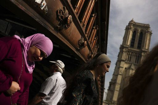 People walk past the Notre Dame cathedral in Paris, Monday, April 22, 2019. In the wake of the fire last week that gutted Notre Dame, questions are being raised about the state of thousands of other cathedrals, palaces and village spires that have turned France - as well as Italy, Britain and Spain - into open air museums of Western civilization.