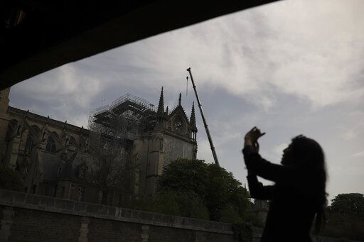 A woman takes photographs of the Notre Dame cathedral in Paris, Monday, April 22, 2019. In the wake of the fire last week that gutted Notre Dame, questions are being raised about the state of thousands of other cathedrals, palaces and village spires that have turned France - as well as Italy, Britain and Spain - into open air museums of Western civilization.