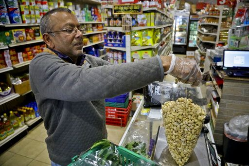 "Dhannitha Meemanage, from Sri Lanka, bags cashews in his family's grocery store, in New York's Staten Island's ""Little Sri Lanka"" community, Monday, April 22, 2019. Sri Lanka's abrupt shutdown of social media sites in the wake of the string of deadly Easter Sunday terror attacks has left worried friends and relatives in places like ""Little Sri Lanka� in the dark. Meemanage, turned to old-fashioned means of getting news about loved ones after the attack, a landline phone."