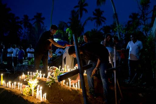 Relatives light candles after the burial of three victims of the same family, who died at Easter Sunday bomb blast at St. Sebastian Church in Negombo, Sri Lanka, Monday, April 22, 2019. Easter Sunday bombings of churches, luxury hotels and other sites was Sri Lanka's deadliest violence since a devastating civil war in the South Asian island nation ended a decade ago.