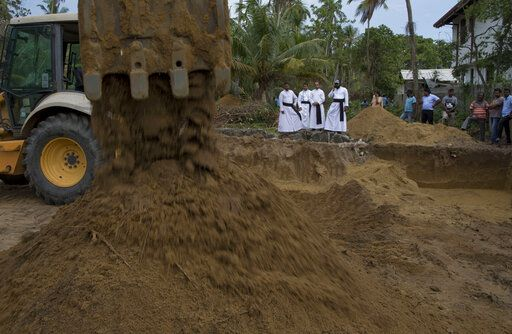 Clergymen watch as an earth mover is used to prepare ground for a mass burial of Easter Sunday bomb blast victims at St. Sebastian Church in Negombo, Sri Lanka, Monday, April 22, 2019. Easter Sunday bombings of churches, luxury hotels and other sites was Sri Lanka's deadliest violence since a devastating civil war in the South Asian island nation ended a decade ago.
