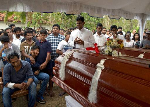Dimitra Silva, fourth left in blue, mourns the death of his brother 13-year old Anos Silva and his grand parents, all died at Easter Sunday bomb blast at St. Sebastian Church in Negombo, Sri Lanka, Monday, April 22, 2019. Easter Sunday bombings of churches, luxury hotels and other sites was Sri Lanka's deadliest violence since a devastating civil war in the South Asian island nation ended a decade ago.