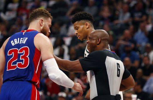 Referee Tony Brown (6) keeps Detroit Pistons forward Blake Griffin (23) and Milwaukee Bucks forward Giannis Antetokounmpo apart during the first half of Game 4 of a first-round NBA basketball playoff series, Monday, April 22, 2019, in Detroit.