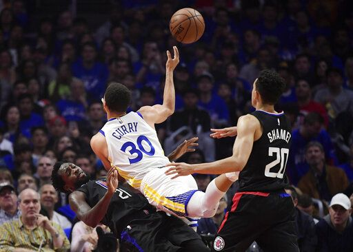 Golden State Warriors guard Stephen Curry, center, runs into Los Angeles Clippers guard Patrick Beverley, left, as he shoots while guard Landry Shamet watches during the first half in Game 4 of a first-round NBA basketball playoff series Sunday, April 21, 2019, in Los Angeles.