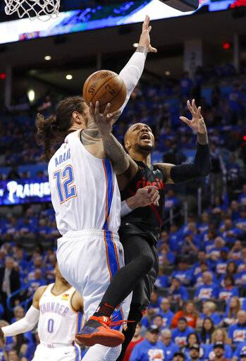 Portland Trail Blazers guard Damian Lillard (0) goes to the basket as Oklahoma City Thunder center Steven Adams (12) defends in the second half of Game 4 of an NBA basketball first-round playoff series Sunday, April 21, 2019, in Oklahoma City. Portland won 111-98. (AP Photo/Alonzo Adams)