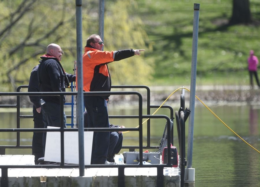Fire department officials operate a sonar unit from a dock as they search a pond Tuesday in Veteran Acres Park in Crystal Lake.