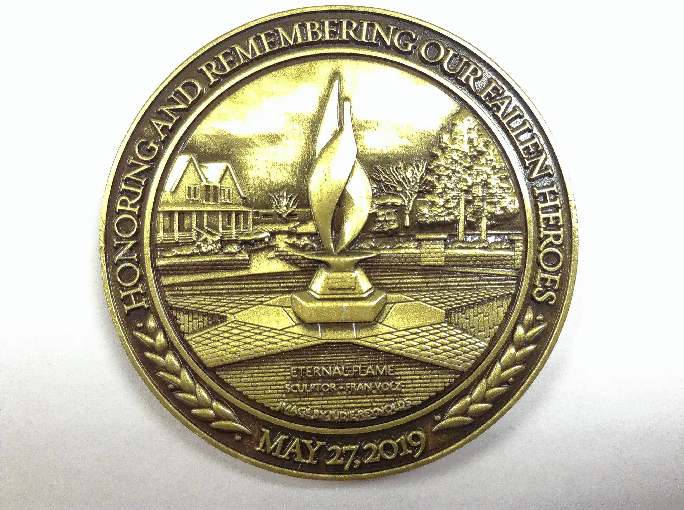 A commemorative coin displays the eternal flame sculpture in Arlington Heights' Memorial Park. The coin is being distributed to fallen hero families, veterans, active military and other supporters.