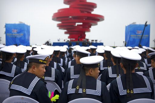 Chinese sailors sit during a concert featuring Chinese and foreign military bands in Qingdao, Monday, April 22, 2019. Ships from Chinese and foreign navies have gathered in Qingdao for events this week, including a naval parade, to mark the 70th anniversary of the founding of the People's Liberation Army (PLA) Navy.
