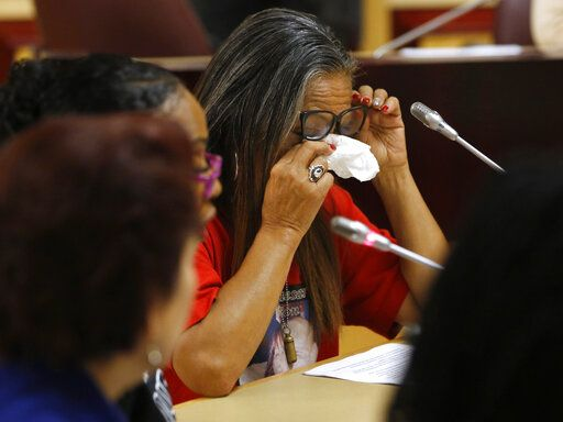Theresa Smith, right, the mother of Caesar Cruz, who was killed in a confrontation with police, wipes her eyes after testifying against a police-backed law enforcement training bill by state Sen. Anna Caballero, D-Salinas, during a hearing at the Capitol Tuesday, April 23, 2019, in Sacramento, Calif. Lawmakers worked to find common ground between law enforcement organizations, which support Caballero's bill and reformers supporting a competing measure, by Democratic Assemblywoman Shirley Weber, that would adopt the first-in-the-nation standards designed to limit fatal shootings by police.