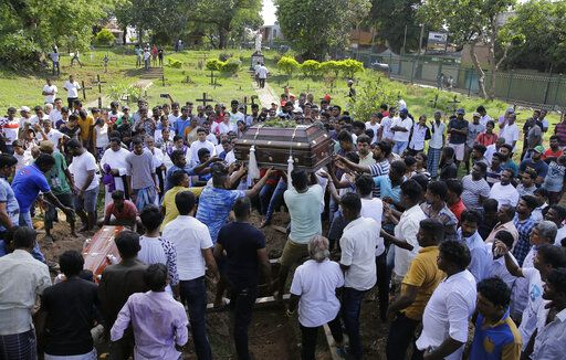 Sri Lankans prepare to bury the coffins carrying remains of Berington Joseph, left, and Burlington Bevon, who were killed in the Easter Sunday bombings in Colombo, Sri Lanka, Tuesday, April 23, 2019. The six near-simultaneous attacks on three churches and three luxury hotels and three related blasts later Sunday were the South Asian island nation's deadliest violence in a decade while Sri Lanka police arrested 40 suspects in the wake of a state of emergency that took effect Tuesday giving the military war-time powers.