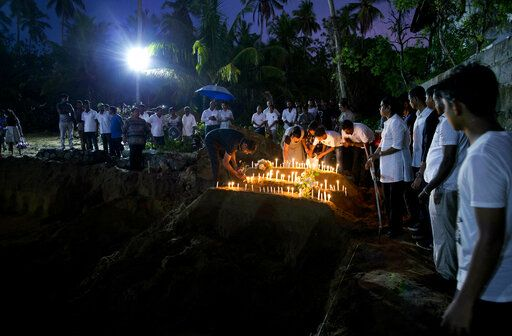 Relatives light candles after burial of three victims of the same family, who died at Easter Sunday bomb blast at St. Sebastian Church in Negombo, Sri Lanka, Monday, April 22, 2019. Easter Sunday bombings of churches, luxury hotels and other sites was Sri Lanka's deadliest violence since a devastating civil war in the South Asian island nation ended a decade ago.